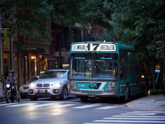 A bus, a motorcycle, and a BMW SUV at a traffic light in Recoleta.