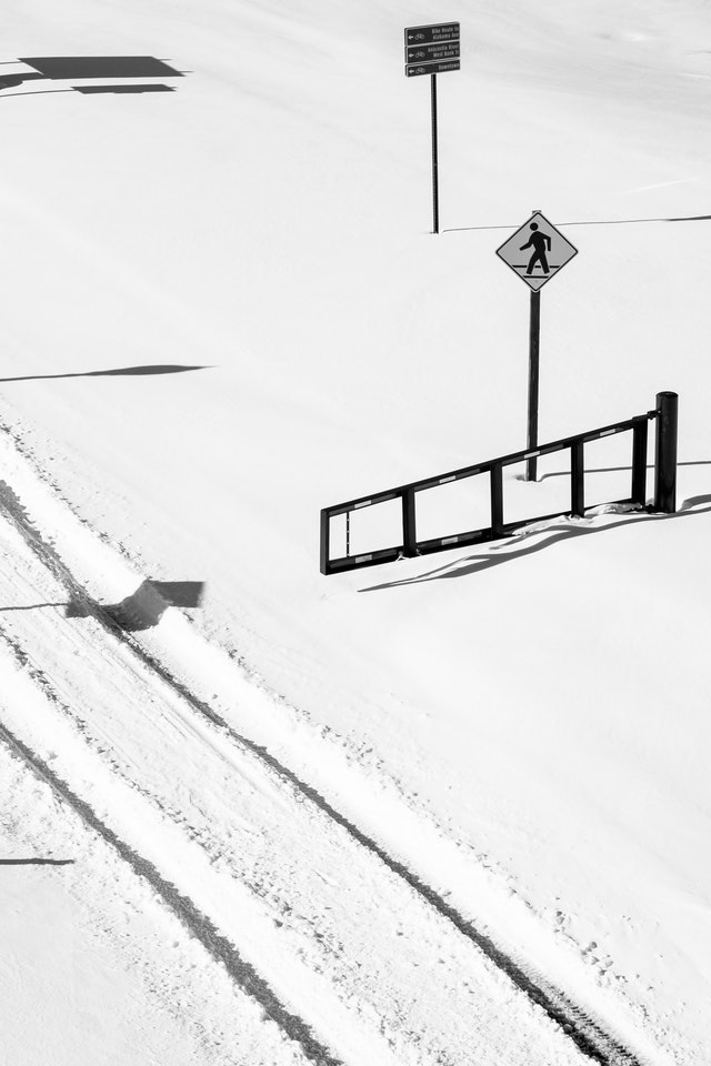 Tire tracks in the snow next to a gate in Anacostia Park.