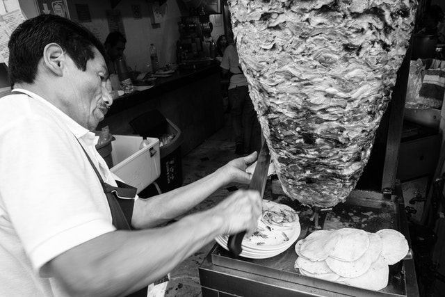 A man shaving off pork from a trompo to make tacos al pastor.