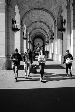 Pedestrians walking along the arches of Union Station.
