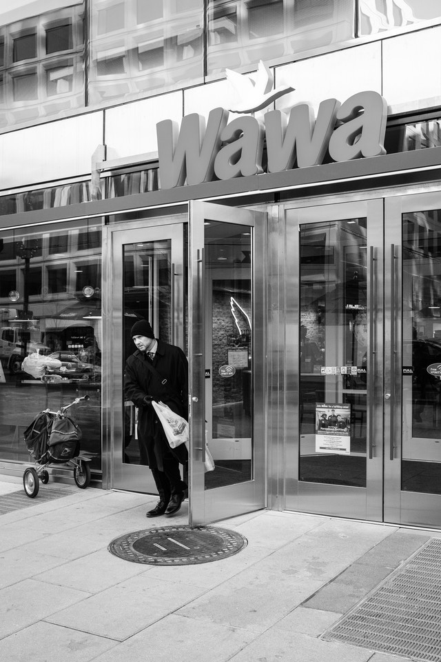 A man walking out of the Wawa on 19th Street NW in Washington, DC.