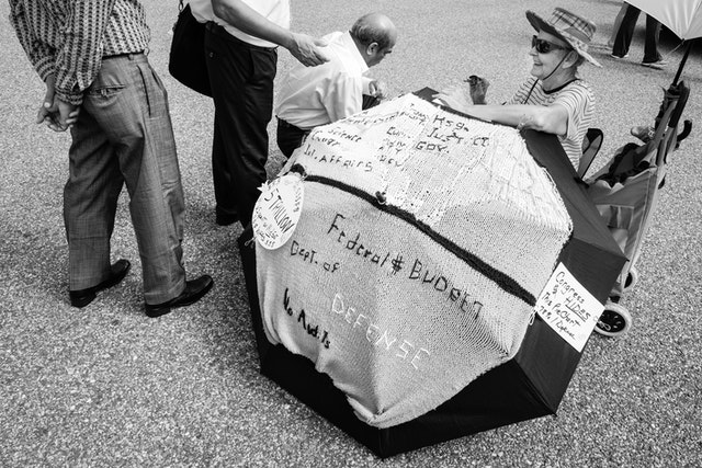 A lady protesting in front of the White House, with signs about the defense budget.