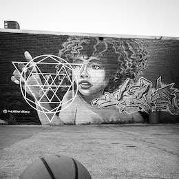 A basketball on a court with a graffiti in the background, in Southside Chattanooga.
