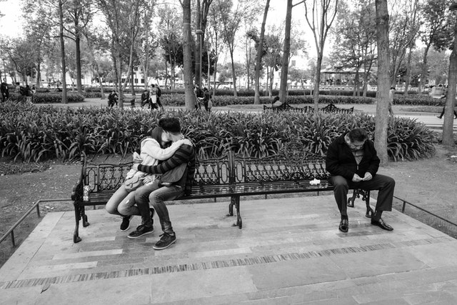 A couple kissing on a bench in the Alameda Central.