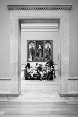 A group of kids sitting on a couch at the National Gallery of Art.
