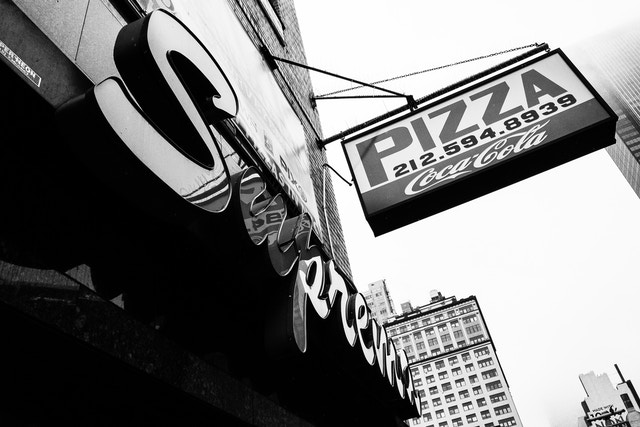 Looking up at the signs of Pizza Suprema on Sixth Avenue.