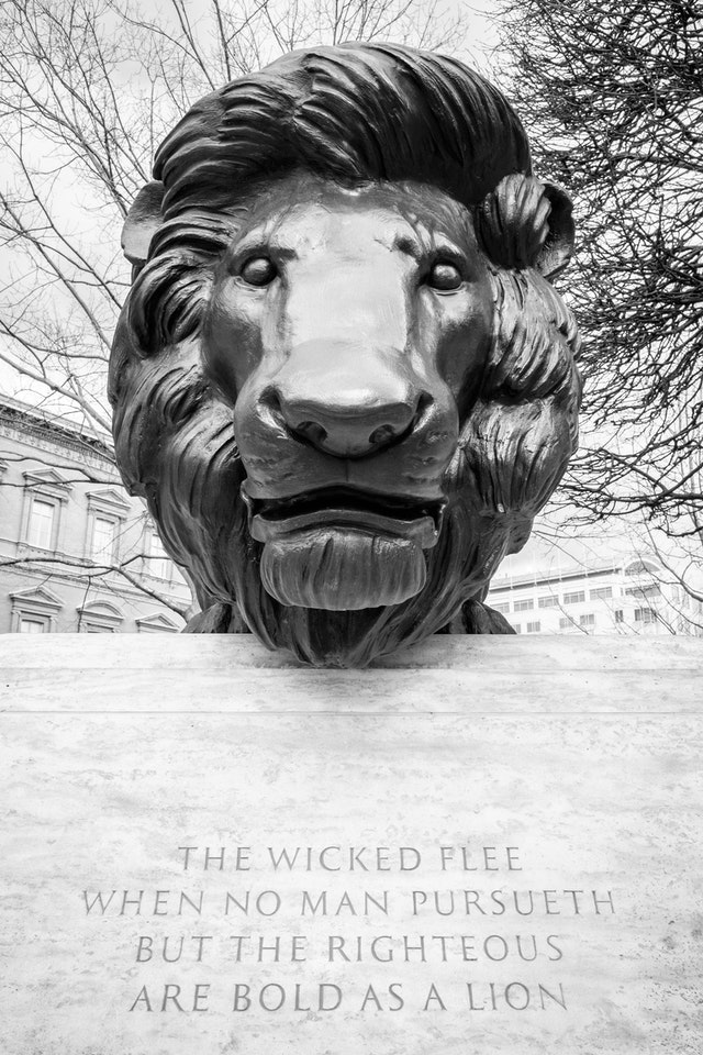 """Sculpture of a lion, over an engraving of """"the wicked flee, when no man pursueth but the righteous are bold as a lion""""."""