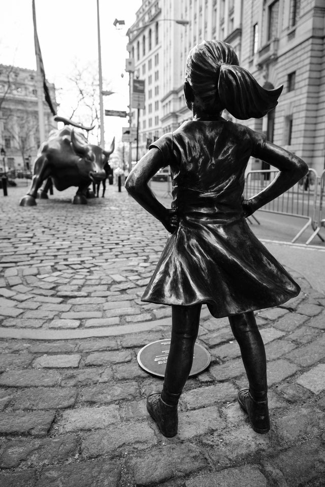 "The ""Fearless Girl"" sculpture in front of the Wall Street Charging Bull."