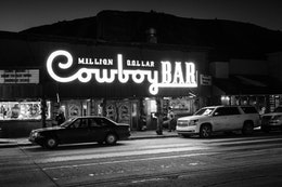 The sign of the Million Dollar Cowboy Bar in Jackson, Wyoming, lit up at night.