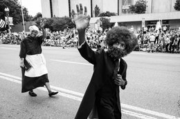 Elijah, a Frederick Douglass reenactor, waves at people at the Independence Day Parade in Washington, DC.