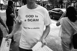 """A man wearing a shirt that says """"god is a scam, don't be a victim"""" while handing out pamphlets that read """"campaign to kill Jesus""""."""