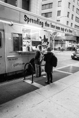 """People buying coffee in front of a coffee truck with a sign that reads """"spreading the love one cup at a time""""."""