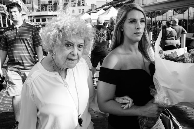 An older woman walking arm in arm with a younger woman holding a bouquet of flowers at Pike Place Market in Seattle.