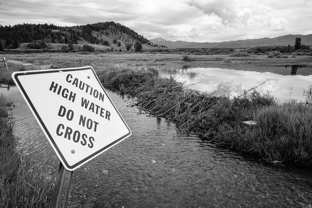 """A road at Elk Ranch, flooded by a beaver damn. In the foreground there's a warning sign that reads """"caution, high water, do not cross"""". In the background, Uhl Hill."""