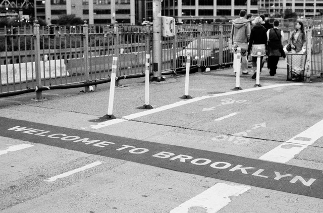 """The """"welcome to Brooklyn"""" sign at the end of the Brooklyn Bridge."""