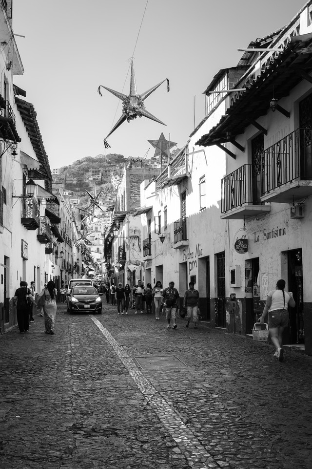 People and cars on a street in Taxco.