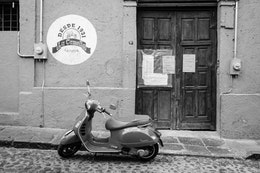 A scooter parked in front of a shut down cantina in San Ángel.