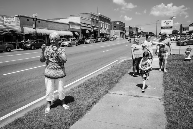 A woman trying on solar eclipse glasses on a sidewalk in Etowah, Tennessee.