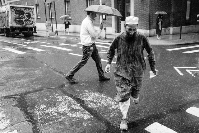 A man smiling while he runs to cross the street in the rain, on William Street in New York City.