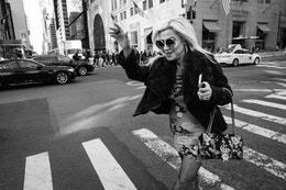 A woman waving and smiling as she crosses the street on New York's Fifth Avenue.