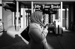 A woman talking on the phone while walking in front of Idle Time Books in Adams Morgan.