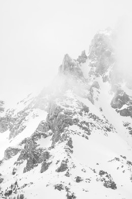 A close-up of a snow-covered peak in the Tetons, surrounded by clouds.