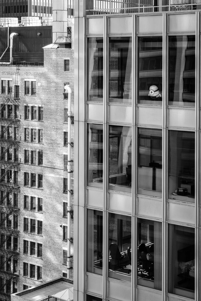 A Minion looking out a window of a skyscraper.