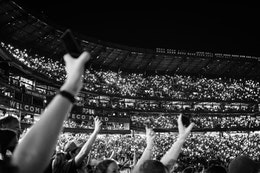 """People raising their phones with the flashlights on, during a performance of """"I Won't Back Down"""" at a Pearl Jam concert."""