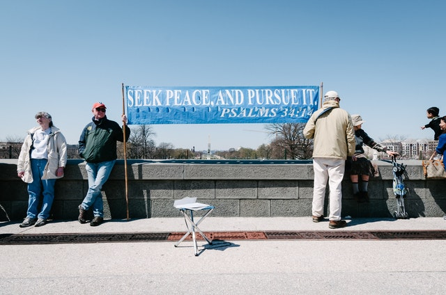 "Demonstrators at the West Front of the United States Capitol building, holding a banner that reads ""seek peace, and pursue it"", from Psalms 34:14."