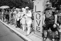 Americans watching the Independence Day parade in Washington, DC. Next to them, a utility box is graffiti'd with LOVE in big letters.