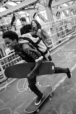 A teenager skateboarding past two pedestrians on the Williamsburg Bridge in New York City.