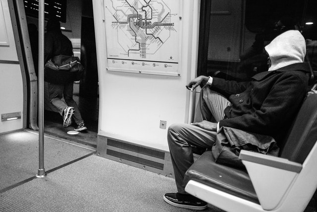 A man sitting on a Metro train while another guy runs out.