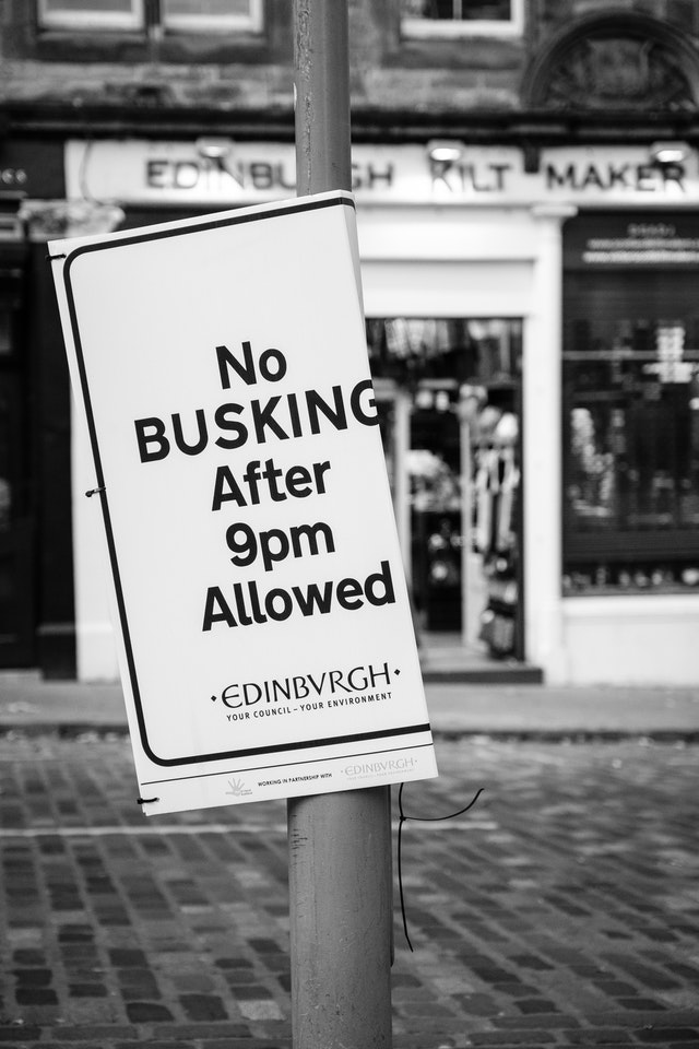 """A sign in Edinbugh's Grassmarket reading """"No BUSKING After 9pm Allowed""""."""