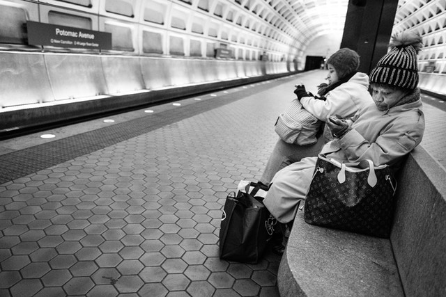 Two women sitting on a bench at the Potomac Avenue Metro Station.