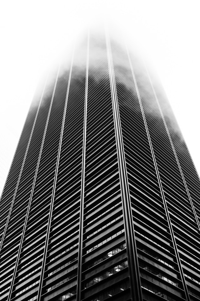 A building in New York's Financial District, with its top completely shrouded in fog.
