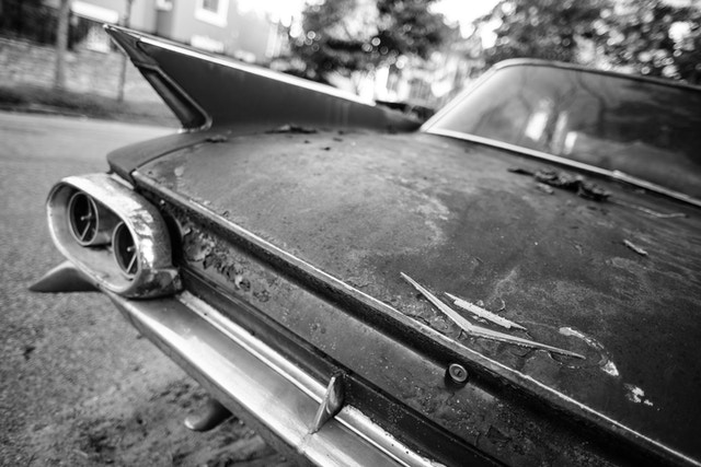 Trunk and left tailfin of a rusted 1960s Cadillac de Ville parked on 9th Street & K Street NE in Washington, DC.