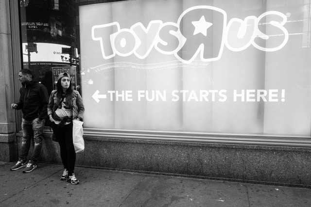 """Two people standing next to a Toys R Us sign that says """"the fun starts here""""."""