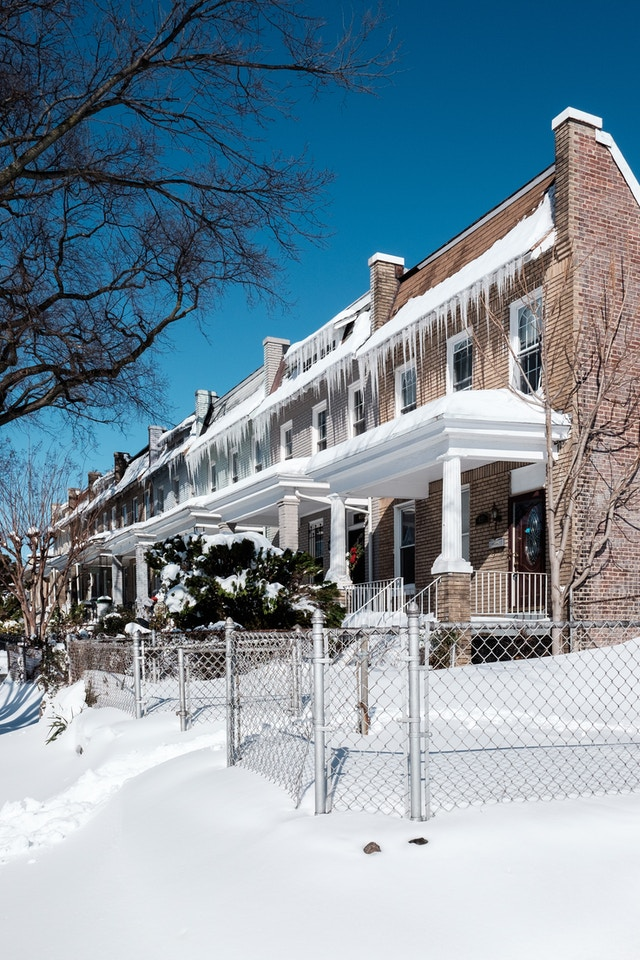 Snow-covered row houses in Capitol Hill, with icicles hanging from their roofs.