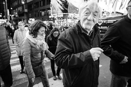A person with a very bushy mustache smiling at the camera and crossing the street near Times Square.
