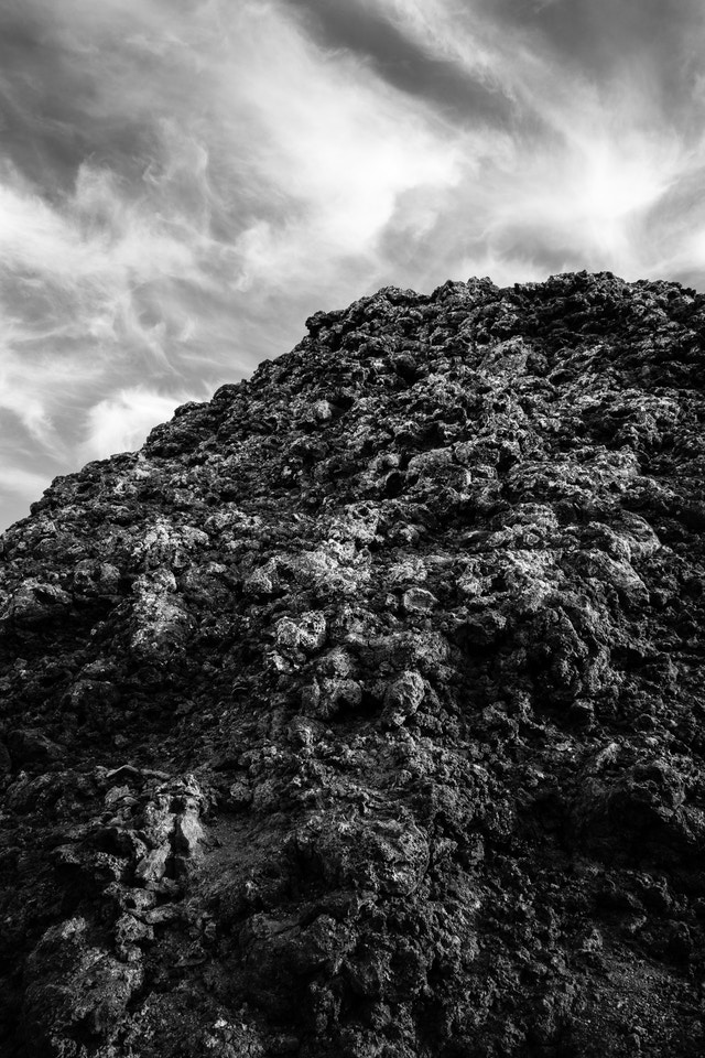The jagged surface of a spatter cone, set against a sky full of wispy clouds.