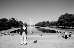 A person dressed as Uncle Sam in front of the Reflecting Pool.