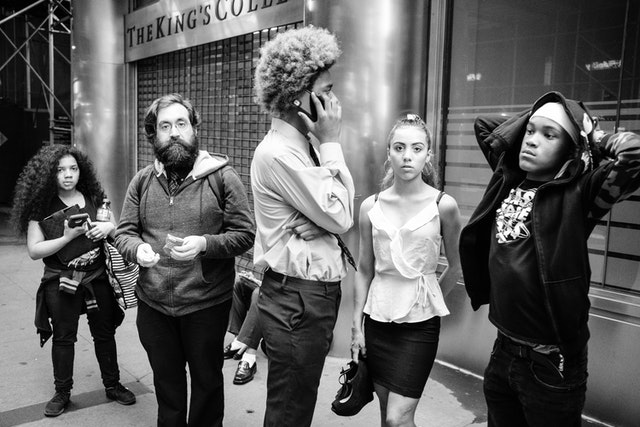 Five people waiting in line for something, on Broadway, in the Financial District.