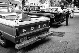 A man in overalls leaning over an old pickup truck parked next to another old pickup truck in Capitol Hill.