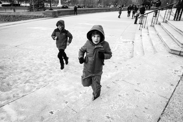 Two kids running on the west front of the United States Capitol building.
