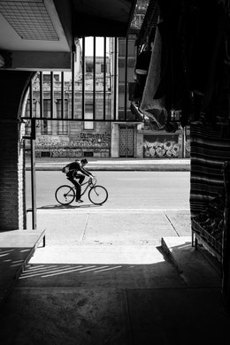 A man riding a bike past an entrance to La Ciudadela in Mexico City.