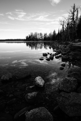 Rocks, trees, and clouds reflected off the waters of Jenny Lake at Grand Teton National Park.