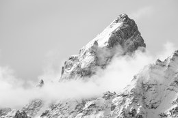 The snow-covered summit of Grand Teton, shrouded in clouds.
