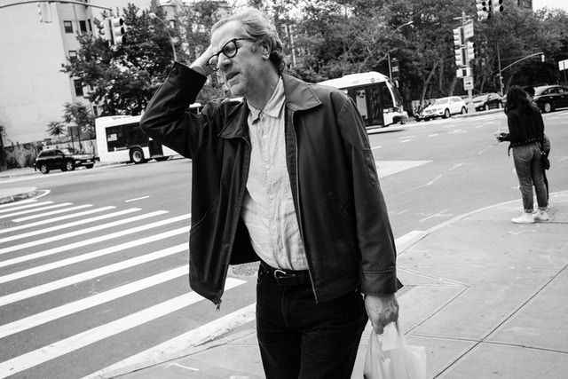 A man carrying a bag and grimacing while walking along East Houston Street in Manhattan.
