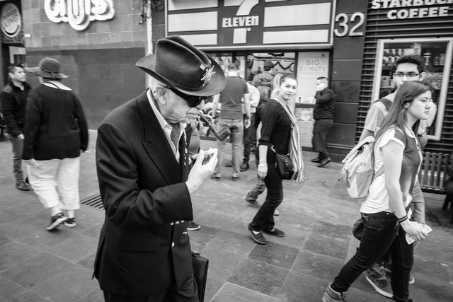 A man in a hat smoking a pipe while walking down the street.