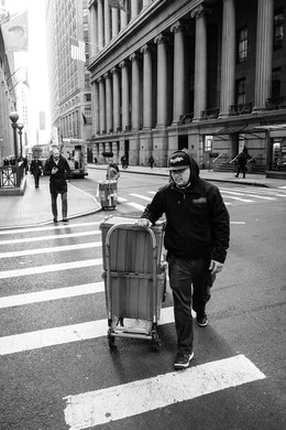 A man pulling a cart on Wall Street, New York.